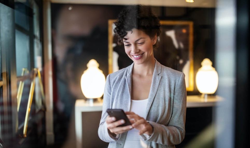 Mulher sorrindo olhando para um celular